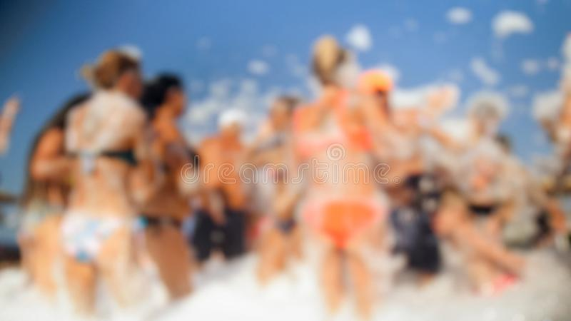 Defocused image of happy people dancing together on beach. Friends having soap foam sea beach disco party. stock image