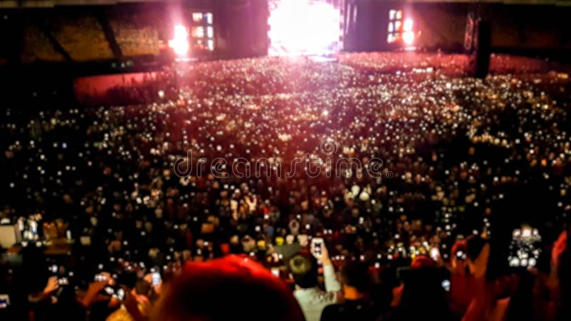 Defocused photo of people listening and watching big rock concert on music festival at big stadium. Crowd of fans stock photo