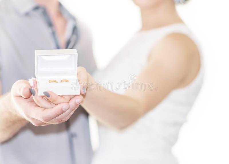 Defocused Porträt junger des coulpe Braut und Bräutigams, die an goldene Hochzeit oder Verlobungsringe in der kleinen weißen Gesc stockfoto