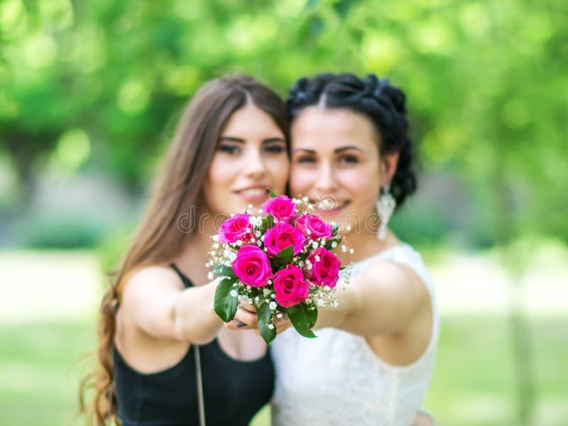 Defocused Porträt von zwei schönen jungen Frauen, die Hochzeitsblumenstrauß zusammenhalten und in Kamera grünem Park betrachten B stockbilder
