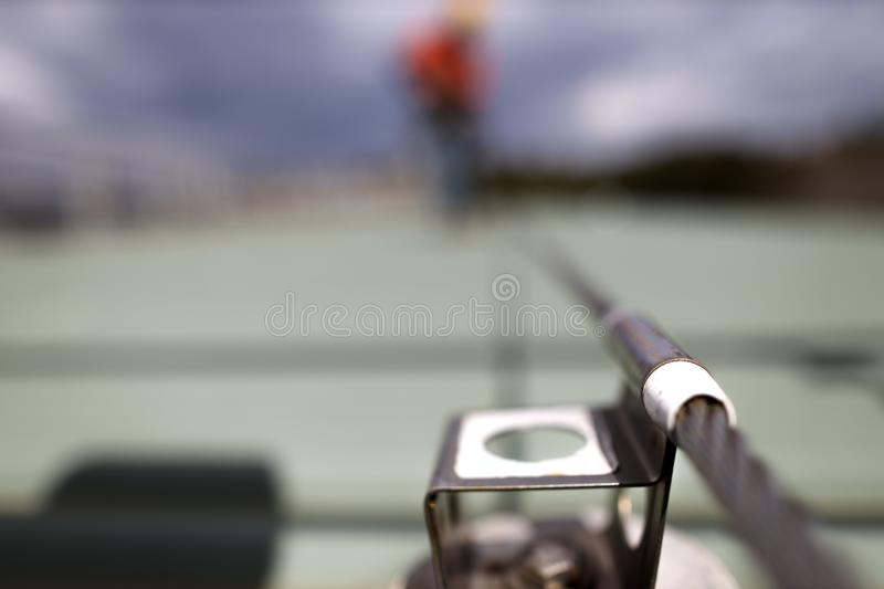 Defocused of rope access inspector technician inspecting fall arrest, fall restraint roof anchor point stock photography