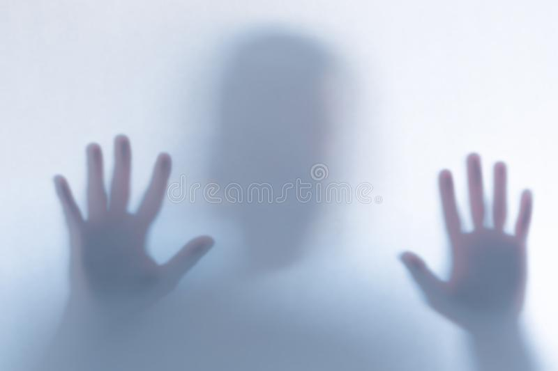 Defocused scary ghost silhouette behind a white glass background royalty free stock photography
