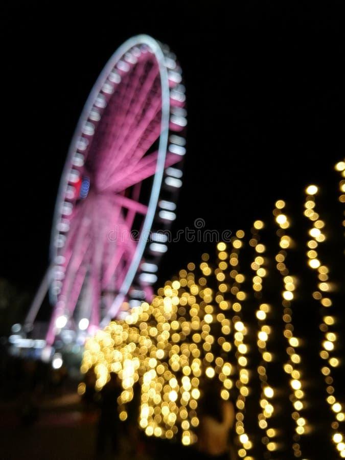 Defocused scena gigant menchii ulotki ferris koło przy nocą z y obraz royalty free