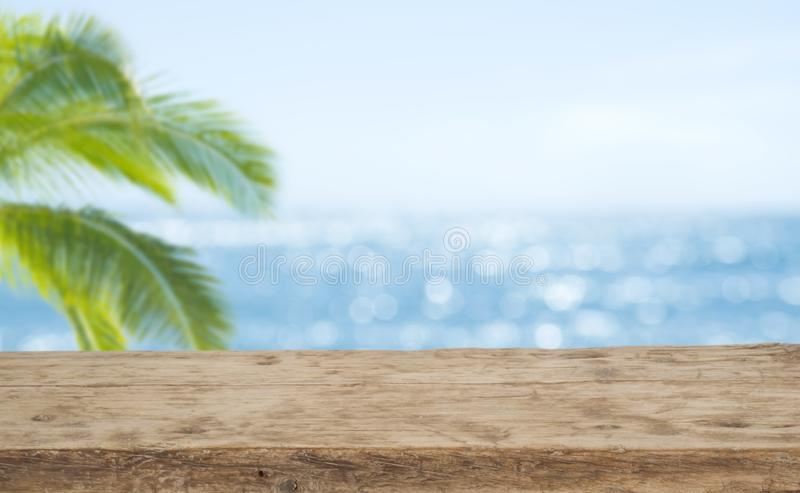 Defocused sea background with wooden table foreground for product display stock photography