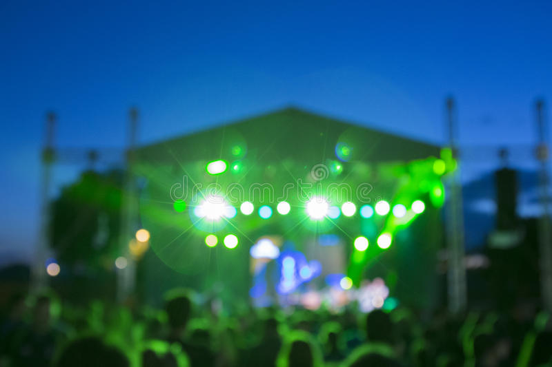 Defocused stage and crowd on a concert. Defocused stage and crowd on rock concert outdoors. Green lights from the stage royalty free stock image