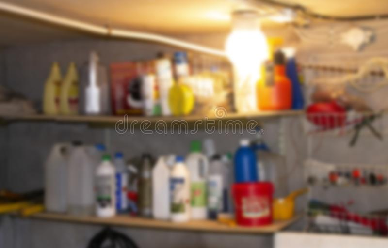 Defocused storage backgrund, many bottles and objects on shelves. Defocused storage background. Old shelves with bottles and cans indoors royalty free stock photography