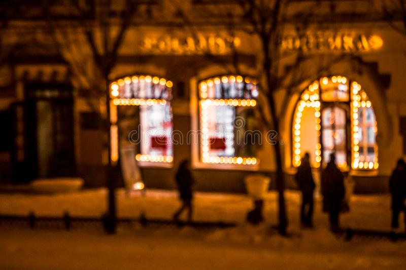 Defocused view of the city street with windows framed with Christmas lights. Night time. Pedestrians walking on the. A Defocused view of the city street with stock photos