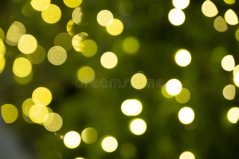 Defocused of yellow bokeh blurred circle light from lighting bulb Merry Christmas   and Happy New Year decorative in the night stock photography