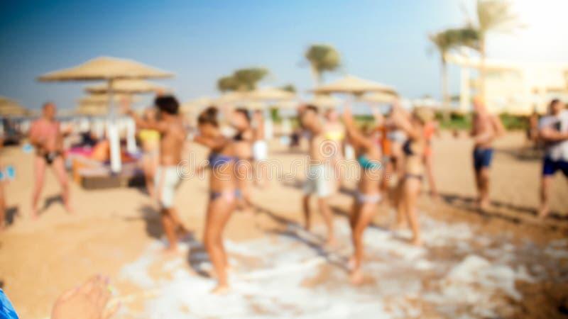 Defocusedbeeld van jongeren die op het overzeese strand bij de discopartij van het zeepschuim dansen royalty-vrije stock foto's
