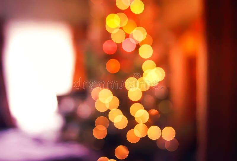 Defocusedligths van verfraaide Kerstboom in het landelijke huisbinnenland Vage Nieuwe jaar feestelijke achtergrond royalty-vrije stock afbeelding