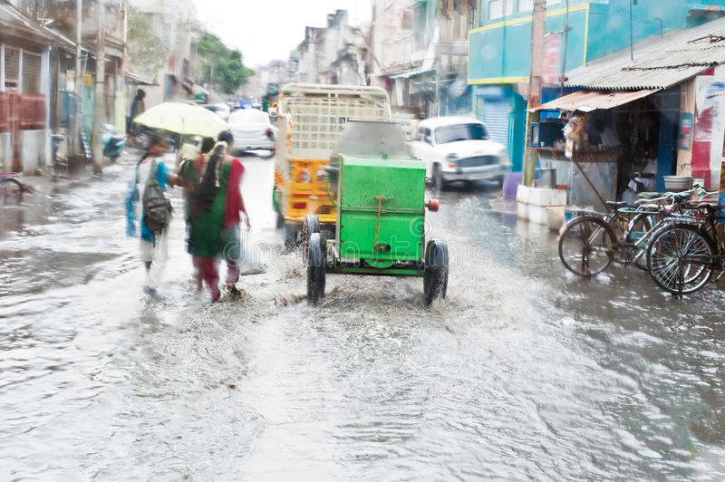 Defocussed view of flash flood at Indian city street. With auto rickshaw, bicycles and pedestrians after monsoon rain. India, Tamil Nadu stock image