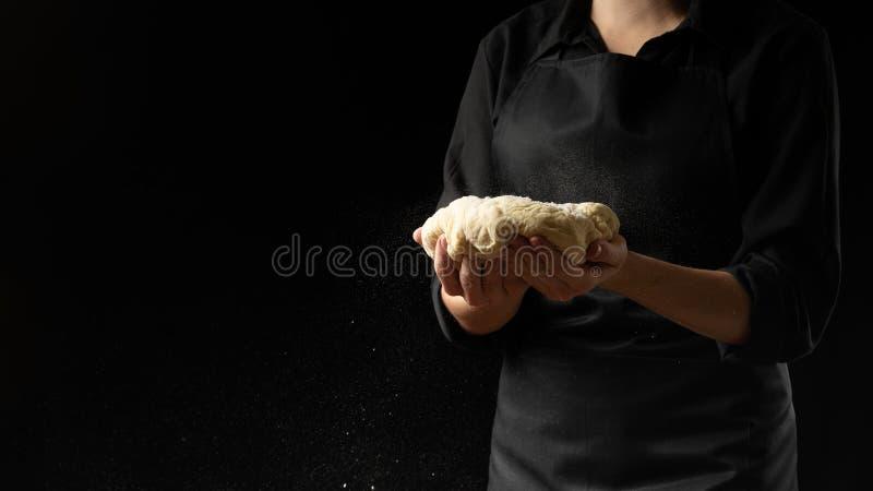 Deg i händerna av kockens chef med mjöl på en mörk bakgrund Begreppet av att laga mat mat, pizza, sötsaker, pastas, bröd royaltyfri fotografi