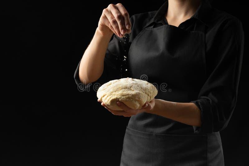 Deg i händerna av kockens chef med mjöl på en mörk bakgrund Begreppet av att laga mat mat, pizza, sötsaker, pastas, bröd arkivfoto