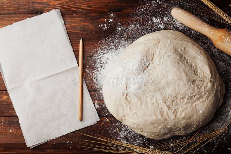Deg med mjöl som bakar papper, kavlen, vete gå i ax på lantlig bästa sikt för tabell Hemlagad bakelse för bröd eller pizza arkivfoto