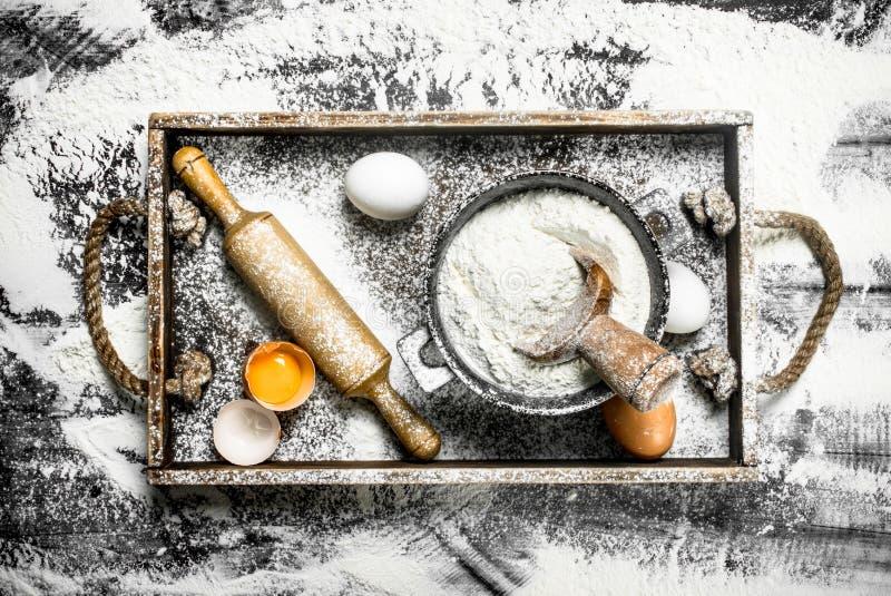 Degbackround Mjöl med ägg och kavlen arkivbilder