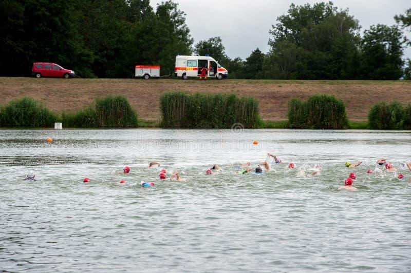 Degensbachsee, Γερμανία, τον Ιούλιο του 2019: Triathlon Ilshofen Κολυμβητές στη λίμνη και το αυτοκίνητο διάσωσης με την εποπτεία  στοκ εικόνα με δικαίωμα ελεύθερης χρήσης