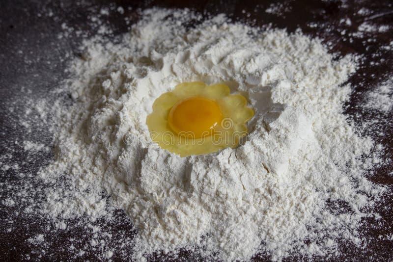 Degförberedelseprocess av att tillfoga ägget till mjölet royaltyfri fotografi