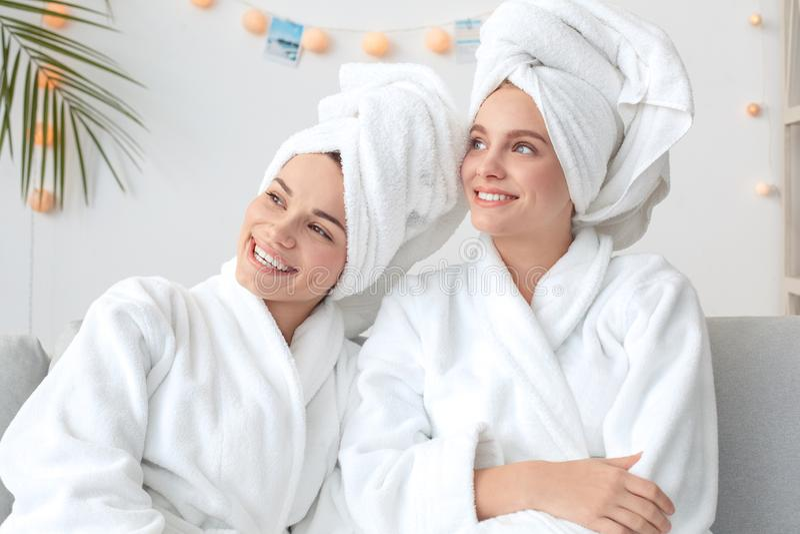Degli amici cura di bellezza insieme a casa che si siede in asciugamani che guardano fuori la finestra dreamful fotografia stock libera da diritti