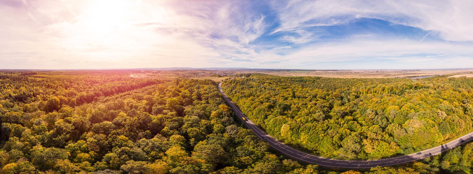 180 degrees scenic landscape of countryside in beautiful autumn sunny day. Aerial drone view of road laid between oak forest royalty free stock images