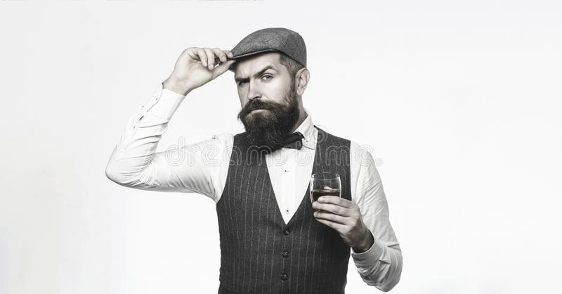 Degustation, tasting. Man with beard holds glass of brandy. Bearded man wearing suit and drinking whiskey, brandy. Cognac. Bearded and glass of whiskey stock image