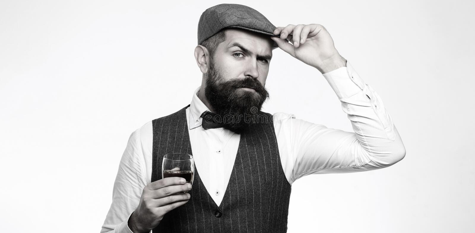 Degustation, tasting. Man with beard holds glass of brandy. Tasting, degustation concept. Bearded businessman in elegant. Suit with glass of whiskey. Sommelier royalty free stock photos