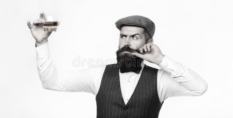 Degustator Mannen med skägget rymmer exponeringsglas av konjak Avsmakning- och degustationbegrepp Skäggig affärsman i elegant drä royaltyfria bilder