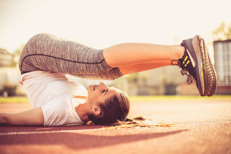 Dehnen Sie aus und errichten Sie Ihre Muskeln Frauenübung stockbild