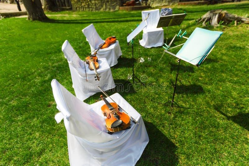 Dehors cérémonie de mariage - les chaises de quartet de ficelle avec l'instrum image stock