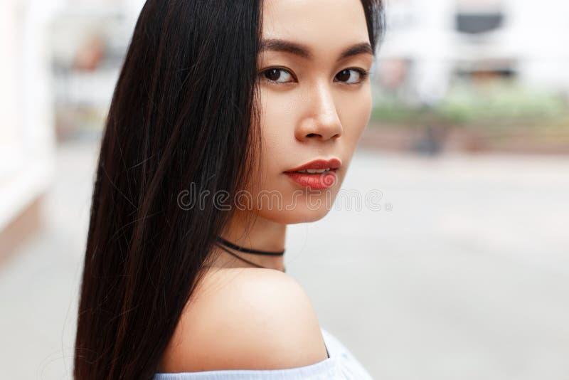 Dehors portrait d'une belle fille asiatique sur le fond image stock