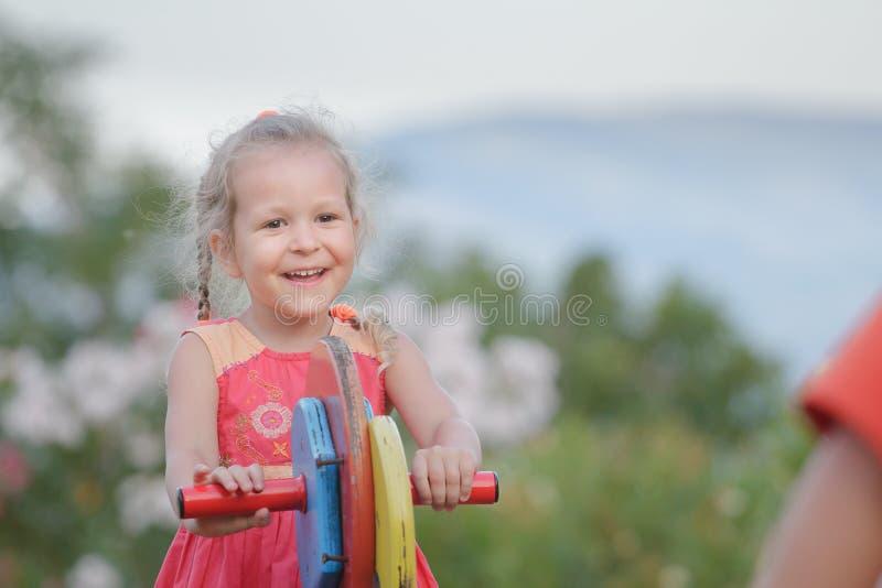Dehors vacances de peu de fille d'enfant balançant sur l'équipement en bois de terrain de jeu photographie stock
