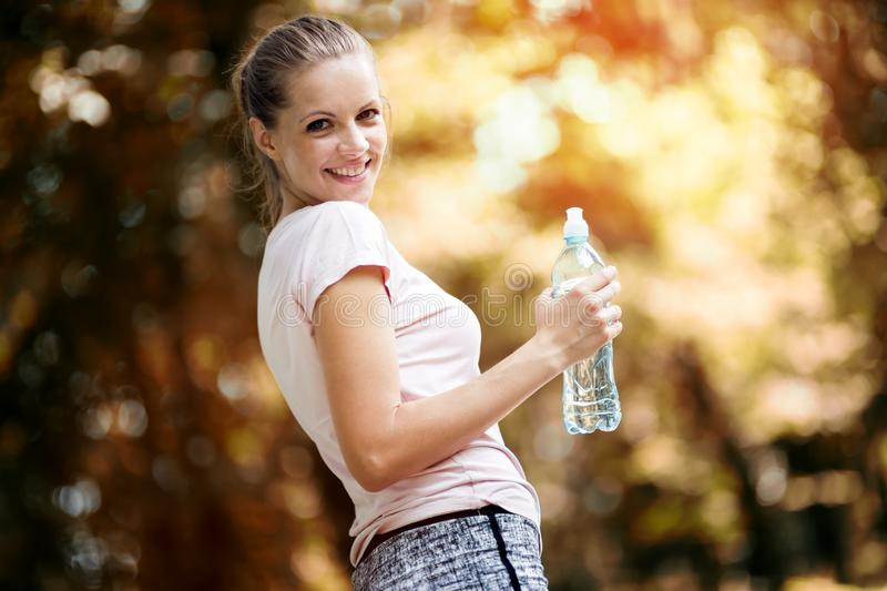 Dehydrated female jogger. Drinking water stock image
