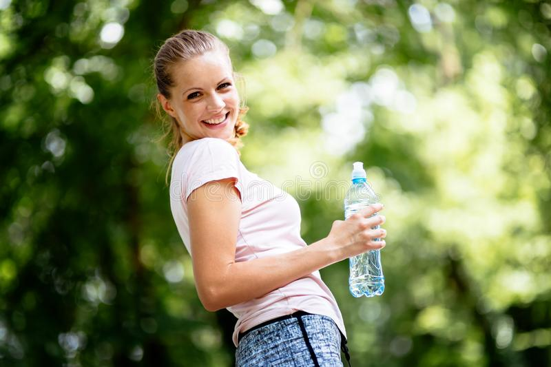 Dehydrated female jogger. Drinking water royalty free stock photos