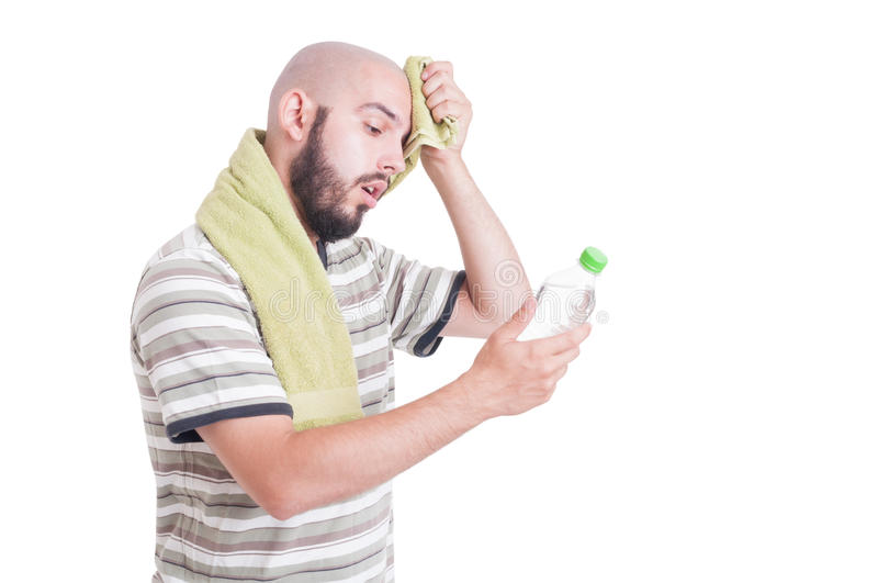 Dehydrated man wiping forehead and holding bottle of water stock photography