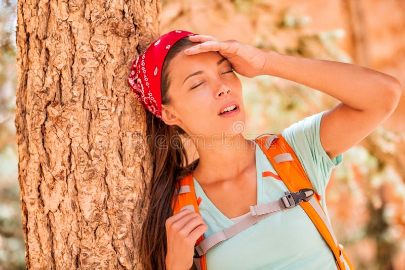 Dehydrated tired hiking woman thirsty feeling exhausted heat stroke. Girl with headache from hot temperature on outdoor activity stock photo
