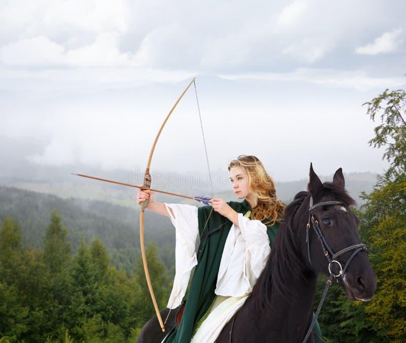 Dei giovani freccia della fucilazione della ragazza a cavallo dall'arco immagini stock libere da diritti