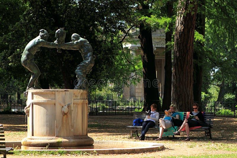 Dei Satiri do famiglia do della de Fontana no jardim de Borghese da casa de campo com as três mulheres que leem no banco próximo fotos de stock royalty free