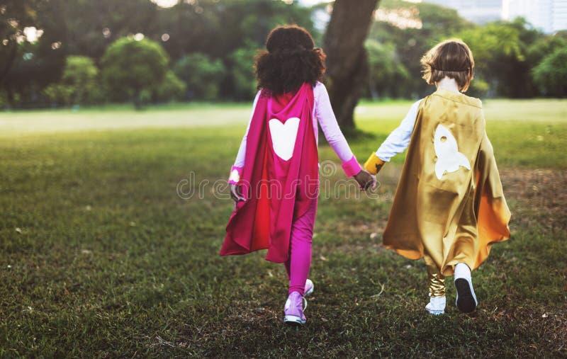 Dei supereroi di retrovisione concetto adorabile del bambino insieme immagini stock