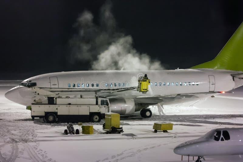 Deicing пассажирский самолет на ноче стоковые фотографии rf