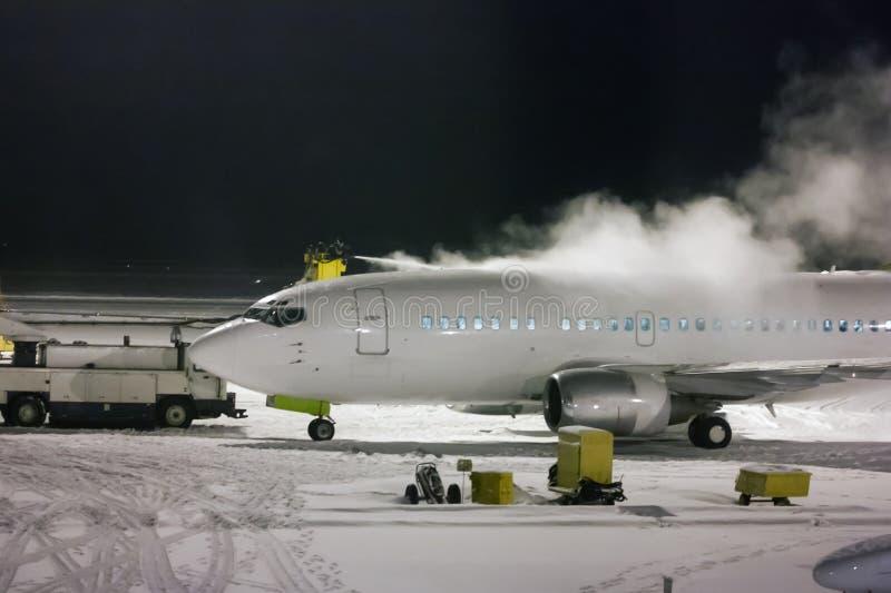 Deicing пассажирский самолет на ноче стоковая фотография rf