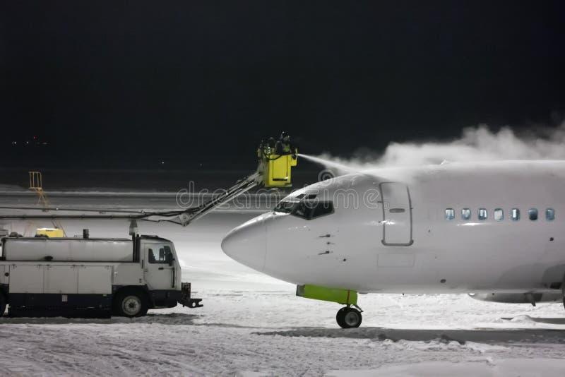 Deicing самолет пассажира на ноче стоковые фотографии rf