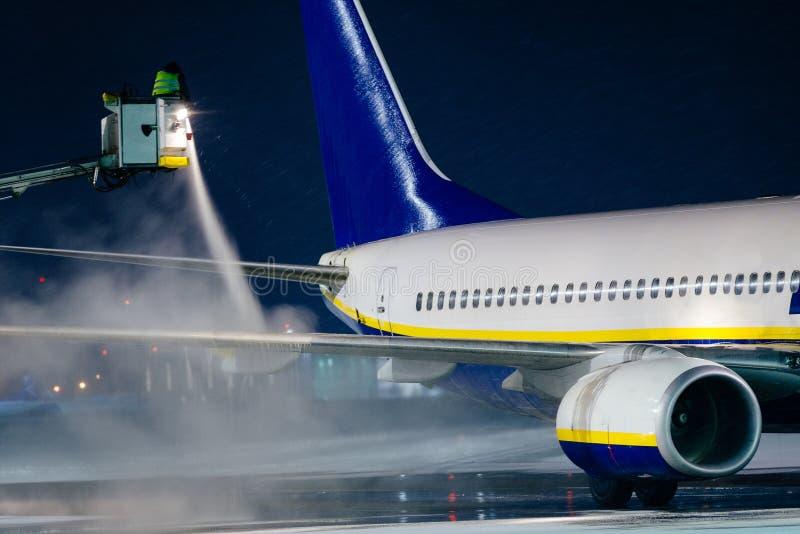 Deicing самолет пассажира во время сильного снегопада стоковое фото