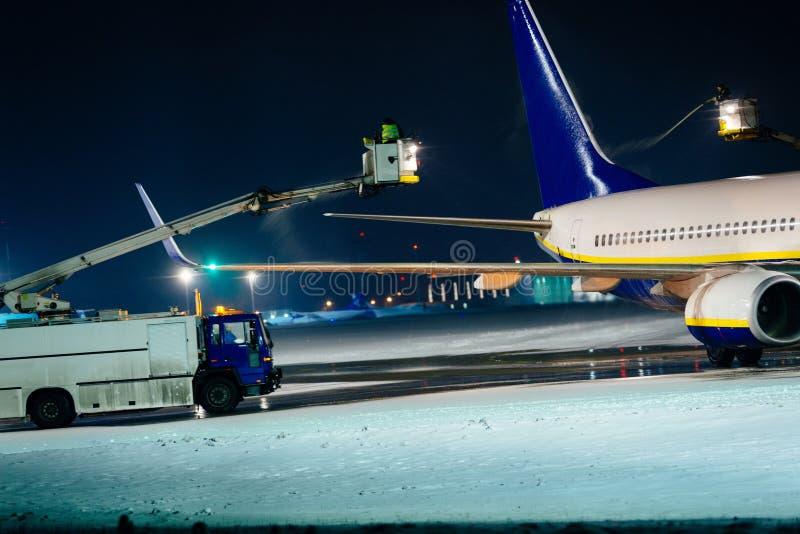 Deicing самолет пассажира во время сильного снегопада стоковое изображение