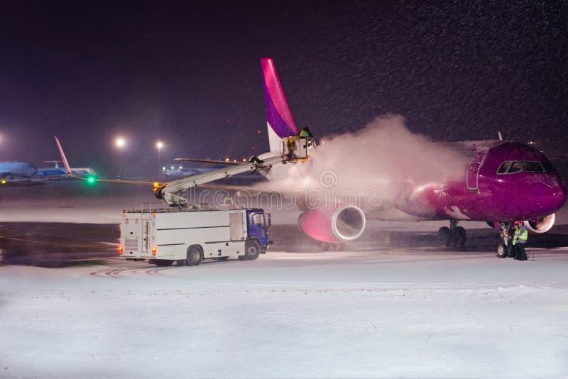 Deicing самолет пассажира во время сильного снегопада стоковые изображения rf
