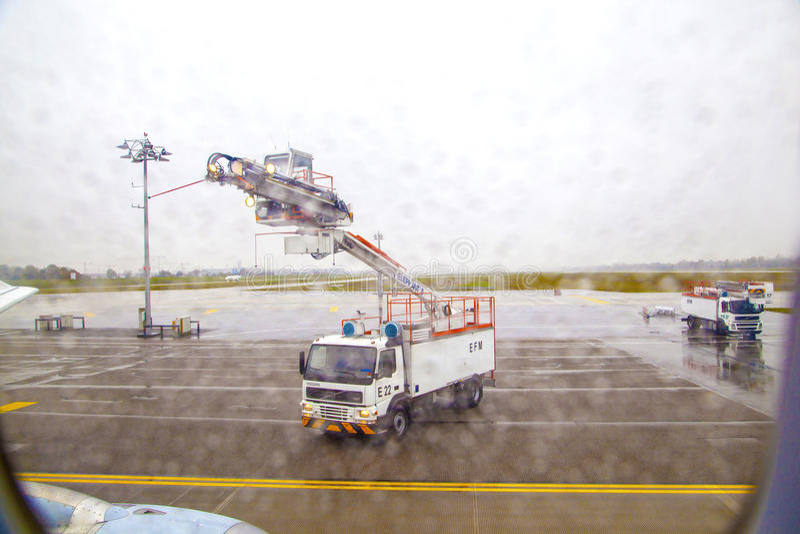 Deicing тележка deices самолет раньше стоковые изображения