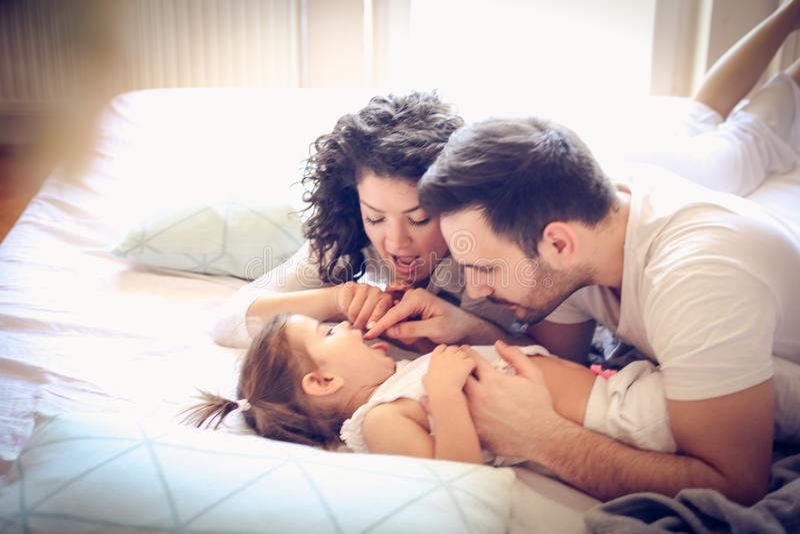 Deixado nós contamos seus dentes Pais novos com sua menina fotografia de stock royalty free