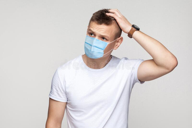 Deixe-me pensar Retrato de um jovem pensável, de camisa branca, com máscara médica cirúrgica em pé, coçando a cabeça e imagens de stock royalty free