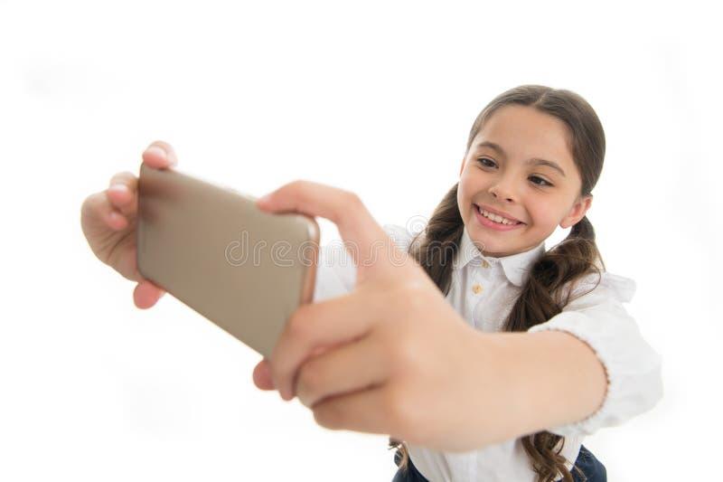 Deixe-me tomar o selfie O cabelo encaracolado longo bonito da menina guarda o smartphone que toma o fundo do branco do selfie Far imagens de stock royalty free