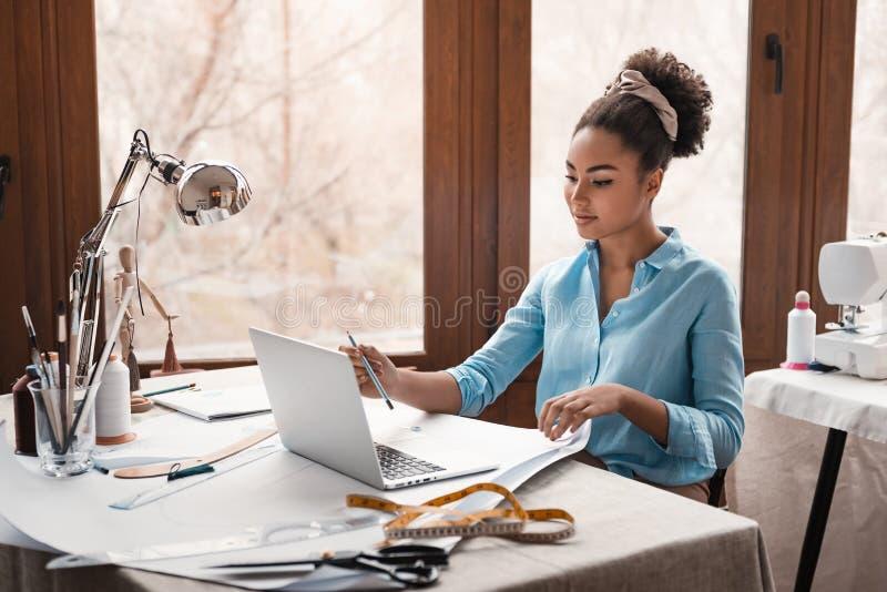 Deixe-nos começar criar Estilista que trabalha com o portátil no estúdio do projeto foto de stock royalty free