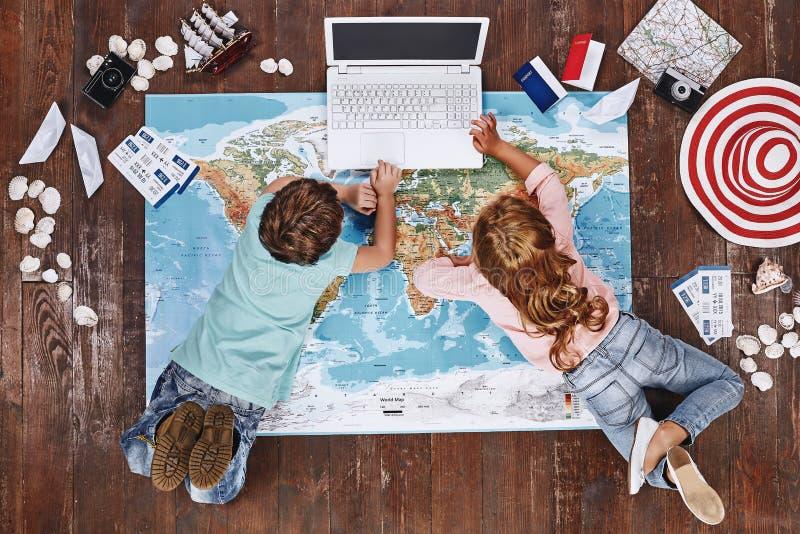 Deixe-nos verificar Crianças que encontram-se no mapa do mundo perto dos artigos do curso e no jogo no computador do brinquedo foto de stock