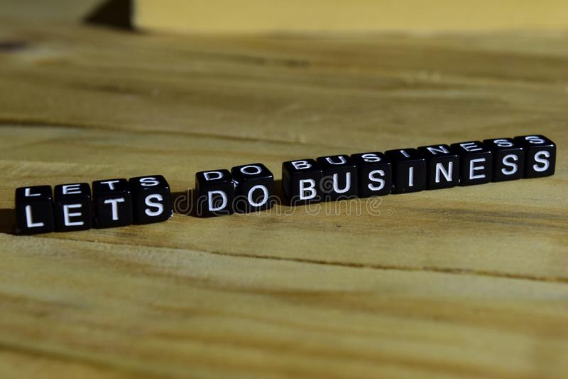 Deixe o ` s fazer o negócio em blocos de madeira Conceito da motivação e da inspiração imagens de stock royalty free